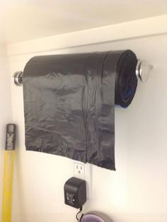 What a great idea for the garage! Trash bags put on a paper towel rack :)