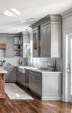 Painted cabinets. Wood floor. Farmhouse sink. Subway tile backsplash.