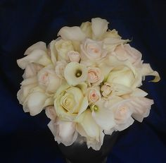 While her girls carried bouquets of red flowers, the bride walked down the aisle carrying a contrasting white version of the same flowers – fragrant garden roses, standard roses with a touch of pink, and white calla lilies.  See more wedding bouquets, centerpieces, and more at www.jeffmartinsweddings.com