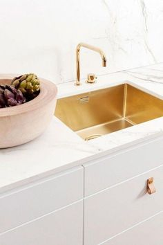 Kitchen with white carrara marble countertops and a gold sink. Yes please!