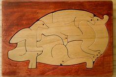 Puzzle in legno di ciliegio di maiale che contiene altri 8 animali. Modello disegnato dal famoso artigiano giapponese Saburo Oguro.   Wood Puzzle Pig: Design Saburo Oguro. The pig is formed by eight different animals. Scroll sawed using cherry wood.