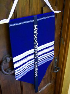 Hanukkah Banner - Vibrant felt and blue-and-white ribbons attached with glue pair up for a warm welcome at the front door. Fold over the top edge of felt and stitch or glue to create a pocket for a dowel. Use stick-on letters to spell out a message on grosgrain ribbon to drape over the banner.