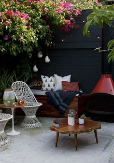 White wire tables, black walls, patio garden idea, raw edge wood coffee table, outdoor fireplace, cushions on a bench