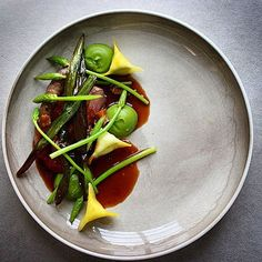 Filé, brisket and sausage from spring lamb. Served with ramson purée, yellow beetroot flowers filled with goat chesse, fried ramson & vild asparagus. Uploaded by @stefanekengren #gastroart