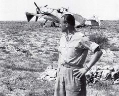 """Major Heinz """"Pritzl"""" Bär and a Bf-109G (""""Gustav"""") photographed on an airfield in Tunisia (April 1943). Hermann Göring's personal dislike of Bär, coupled with Bär's insubordinate character and lack of military discipline, deprived him of the diamonds to his Knight's Cross of the Iron Cross with Oak Leaves and Swords. After World War II, he continued his career as an aviator, and he was killed in a flying accident on April, 28, 1957. Note his Afrika Corps wristwatch."""