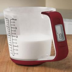 A cup that measures both weight and volume of liquids and solids
