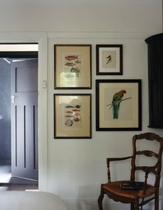 A group of paintings in a corner of the bedroom includes an Eastern Rosella painted by Ridgway and a pair of hand-coloured 18th century marine engravings.