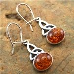 Drop earrings of warm and mysterious amber, nestled in silver, dangling from a silver Celtic knot... Purchase at www.FashionJewelry.com