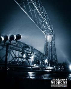 Duluth Aerial Lift Bridge Under Driving Rain by Mark David Zahn Photography (formerly Shutter Happens Photography). The Aerial Lift Bridge in Duluth Minnesota lit up during a nighttime severe thunderstorm. Driving rain, wind and lightning pounded Canal Park this night in May 2012.