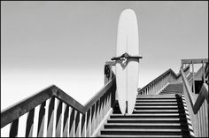 Man holding a surfboard on beach steps in Corona Del Mar. California, USA. 1968. © Dennis Stock / Magnum Photos