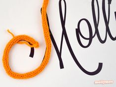 """Craft ideas for using I-cord or """"French knitting"""" or """"spool knitting"""" by Michelle McInerney of MollyMoo. Here: make a cord, and couch it down to make a raised monogram. Or fill the cord with a wire to make a freestanding word or name."""
