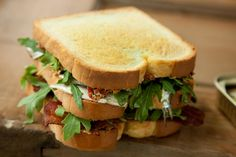 A club sandwich recipe made with sardines, bacon, arugula, and sun-dried tomato butter.