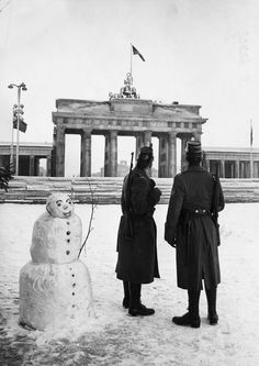 Two West Berlin policemen on duty with new American rapid fire rifles (and a snowman). Christmas Day, the Berlin Wall at the Brandenburg Gate, 25th December 1961.
