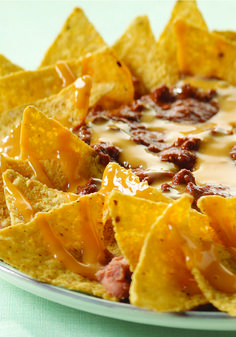Nacho Platter Ole – Canned chili and cheese sauce are heated and poured over refried beans and tortilla chips in this savory snack idea and appetizer recipe!