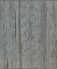 Thin wooden planks in consistent grey color set in vertical formation.