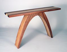 An elegant console in African mahogany. Top and legs are striped down the center with a blond band of stack-laminated Baltic birch that features the cut of the layers. $2800.00