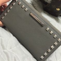 Gray w/ Silver Studded Hardware Ava Wallet Gray w/ Silver Studded Hardware Ava Wallet. Great used condition. Opens like an accordion. Normal wear on hardware but unnoticeable without looking for it. Love this wallet but time for a change. Rebecca Minkoff Bags Wallets