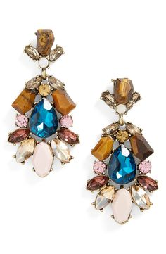 Clusters of crystals and stones shimmer on elegant drop earrings that call to mind vintage styles.