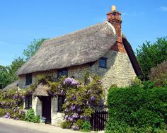 Light stone cottage. Thatched roof. Surrounded by a garden of flowers. in the middle of the forest and a small stream behind the cottage