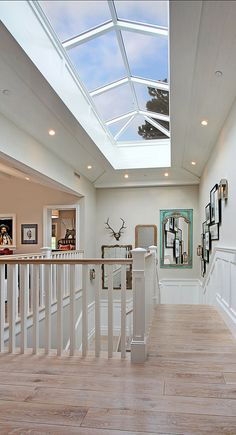 Coastal Home - A x custom skylight over the staircase atrium highlights the grandiose scale of the interior and brings even more light into home. Attic Remodel, Attic Renovation, Coastal Homes, Coastal Cottage, Coastal Farmhouse, Farmhouse Plans, Luxury Interior Design, Stairways, My Dream Home
