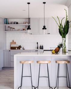 grey and white kitchen, high stools, wire legs, black pendents, floating shelves, white subway tile