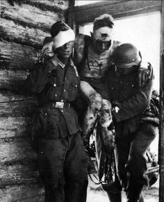 Eastern Front, 1941: A severely wounded German soldier, with visible head, chest and lower extremity wounds, is carried to the field station by two comrades, one wounded in the head as well. German casualties increased geometrically once the battle with the Russians heated up. The trend continued without mercy until the total destruction of the German army in the East.