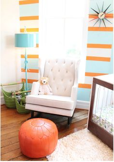 A neutral nursing chair and rug work well with a bright palette on the walls of your nursery.