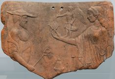 A terracotta tablet from Locri, Calabria, . 475—450 BC, depicting two Greek gods with their symbolic attributes: Hermes (petasos and caduceus) and Aphrodite (a flower and Eros) .(Photo: Egisto Sani via State Antique Collection, Munich & ancientrome.ru)
