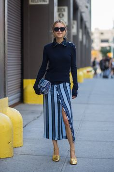 A slim top is untucked here, but still works with the skirt's longer-length. The slit in the wrap skirt is key here for dialing up the vamp-factor. #refinery29 http://www.refinery29.com/midi-skirt-outfits#slide-5
