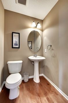 Traditional Powder Room with Powder room, Ceramic pedestal sink, Hardwood floors, Odelia oval bevel frameless wall mirror