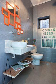 O cinza da parede deste lavabo vem do revestimento escolhido pelo escritório Martinhão Neves Arquitetos. Repare que o espelho é como um mosaico de peças simples e pequenas.