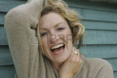 A blonde woman in her thirties holding up her hair and laughing at the camera Stock Photo