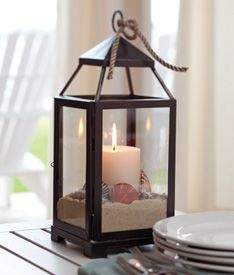 Place a pillar candle in a lantern, then surround with it sand. Add a few small seashells and tie a piece of rope onto the handle. ~s~