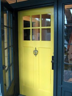 """Cass, blogger from That Old House, describes the hue of her front door as """"summer squash yellow."""" It's actually Benjamin Moore Imperial Yellow, which pops out like a happy surprise from behind the charcoal-colored screen door frame and trim."""