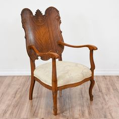 This antique armchair is featured in a solid wood with a gorgeous quarter sawn wood finish. This chair is in great condition with an intricate carved back, curved details and white floral upholstered seat cushion. Unique chair perfect for an eclectic living space! #eclectic #chairs #armchair #sandiegovintage #vintagefurniture