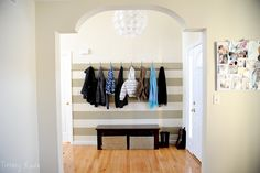 The simple grey and white stripes here look so elegant with uniform hooks in the molding. The nice thing about an entryway is that you can commit to a paint job like this because its small size makes do-overs easy. Entryway Organization, Entryway Ideas, Garage Entryway, Bench With Storage, My Dream Home, Mudroom, Decorating Your Home, Sweet Home, New Homes