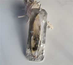 I handcrafted a bold sterling pendant to showcase this exquisite plume agate. I reticulated the silver, more heavily at the base, to echo the variations the inclusions give the stone. I opened up the silver both to reduce the weight of the piece and to better display the rich markings in the translucent stone. The one-of-a-kind agate is milky white and displays inclusions in shades of black and grey with touches of gold.   A simple square wire bail will let you hang this beauty from a…