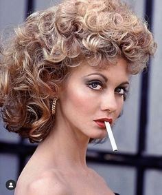 """Lovely Australian singer Olivia Newton-John as Sandy in a promotional shot for """"Grease"""" - in her bad girl persona wearing big hair and foxy makeup with an unlit cigarette between her sexy red lips! Grease Sandy, Sandy Makeup Grease, Olivia Newton John Grease, Grease 1978, Grease Movie, Musical Grease, Grease 2, John Travolta, Look Disco"""