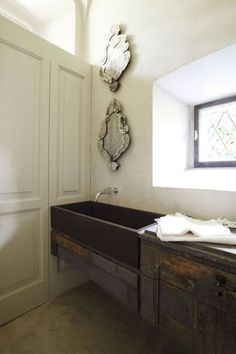In a bathroom, De Cotiis pairs a stone trough sink and antique rustic cabinetry with Baroque mirrors.