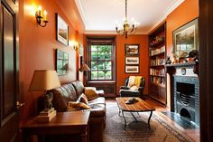 Living room with burnt orange walls - David Giral Photography Orange Rooms, Living Room Orange, Orange Walls, Red Walls, Wood Trim Walls, Dark Wood Trim, Oak Trim, Stained Wood Trim, Interior Trim