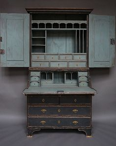 Period baroque secretary in two parts with elaborately fitted interior, Sweden circa 1750.The upper section, in addition to its drawers and compartments, has two candle slides in its base. The lower section has a slant front above a narrow pencil drawer and two over two box drawers. The interior has an unusual storage compartment built into the writing surface. Original hardware includes incised brass escutcheons and an interesting catch for the library doors. Simple bracket base.