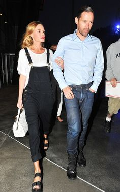 Kate Bosworth wearing black cuffed overalls, white t-shirt, and black sandals