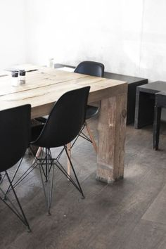Rustic light wooden table with surrounding dark or black chairs and furniture.