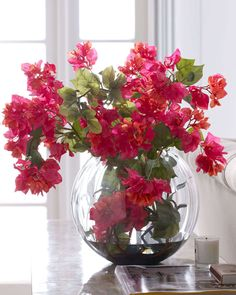 "Handcrafted bougainvillea arrangement. Clear glass bowl. Poly silk bougainvillea vines. Acrylic ""water."" 33""W x 15""D x 22""T. Imported."