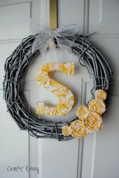 Yellow and gray initial wreath: spray painted wreath, wooden initial wrapped in fabric, fabric flowers.