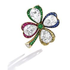 Gold, Diamond, Colored Stone and Colored Diamond Brooch Designed as a four-leaf clover, the leaves set with four pear-shaped diamonds weighing approximately 9.35 carats, the stem and leaves accented by calibré-cut emeralds, sapphires and rubies, further decorated with French-cut diamonds of brownish yellow hue, centered by one round emerald, the stem completed by one pear-shaped diamond.
