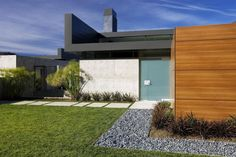 Frosted Glass Entrance Door Design Following The Concrete Path On The Green Court Also Pebbles And Plants Modern Black House with Orange Accents Home design