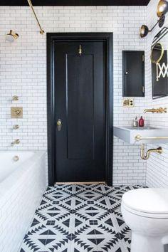No piso, azulejos geométricos. Na parede, tijolos brancos. Na banheira, mármore. Parede preta e objetos dourados finalizam a decoração.