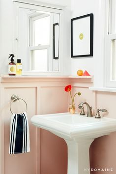 A small bathroom with pink walls, and touches of gold, black and white