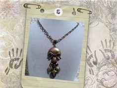 Colgante de forma de calavera color bronce con piedrecitas negras y cadena bronce metal (hierro)